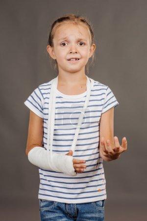 Photo pour Surpris et triste fille avec bras cassé est debout sur le fond gris et en regardant la caméra. Elle a tendu son bras vers l'avant. - image libre de droit