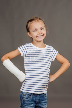Young happy girl with broken arm is standing on the gray backgro