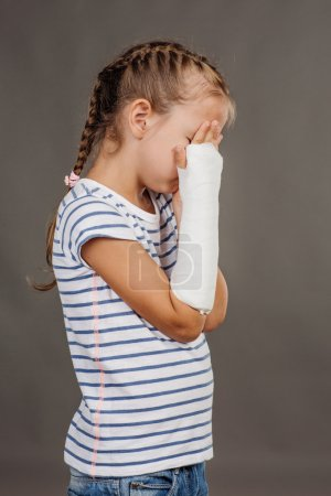 Sad girl with broken arm is standing on the gray background. Med