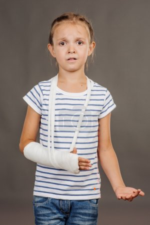 scared girl with broken arm is standing on the gray background.