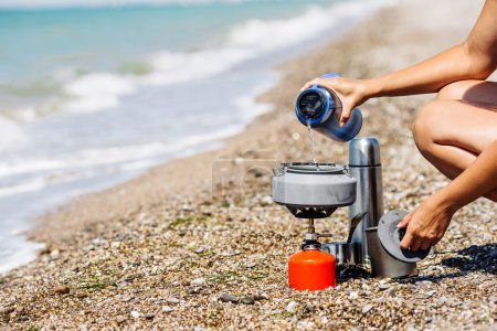 Woman boiling water on camping stove on sea shore. bushcraft equipment