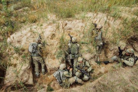 Photo pour Groupe de guerriers se cachant dans les tranchées et tirant - image libre de droit