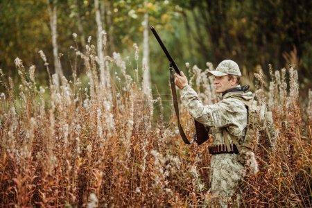 man hunter with shotgun in forest