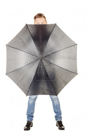 young man hidden in umbrella against white background