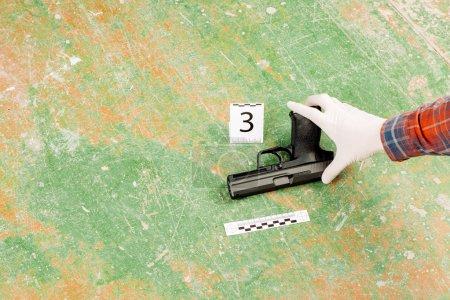 criminalist preventing gun at the murder scene
