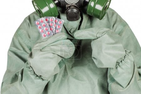 Man with protective mask and protective clothes holding out pill