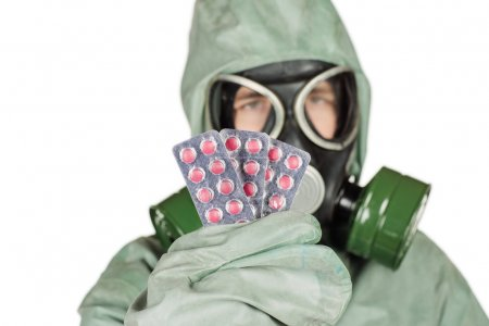 Man with protective mask and protective clothes holding out pills in her hand
