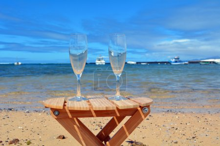Celebration with two glasses of champagne on the paradise beach