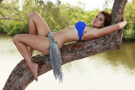 Brunette in swimsuit posing on branch