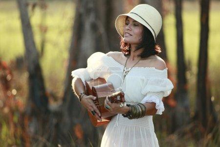 Brunette fille jouer de la guitare dans les bois