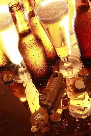 Photo pour Bouteilles de bière dorées rétro-éclairées, verres, ouvre-bouteille et capsules - image libre de droit