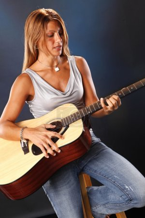 Girl playing on an acoustic guitar