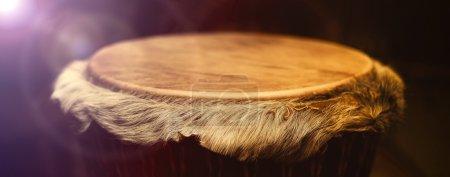 Photo pour Origine africaine djembe tambour avec lame en cuir avec des cheveux magnifiques en lumière jaune violet bel effet avec fond sombre - image libre de droit
