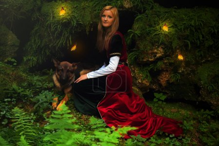 A beautiful woman fairy with long blonde hair in a historical gown, with dog