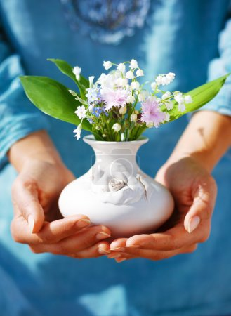 Woman holding bouquet of flower in vase. Blue clothing background