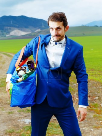 young handsome groom in blue suit with a bag full of beer bottles.