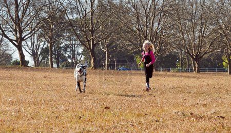 girl with dog running in field