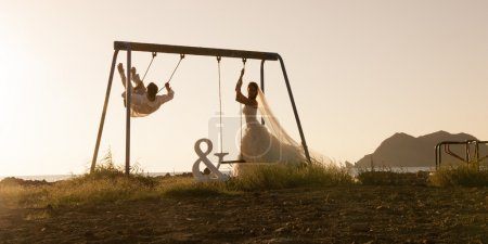 Foto de Hermosa recién casada pareja de columpios al aire libre, concepto de boda romántica - Imagen libre de derechos