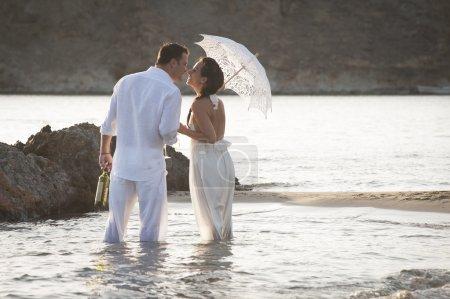 Photo pour Couple debout dans l'eau de mer avec bouteille de vin, femme tenant parasol - image libre de droit