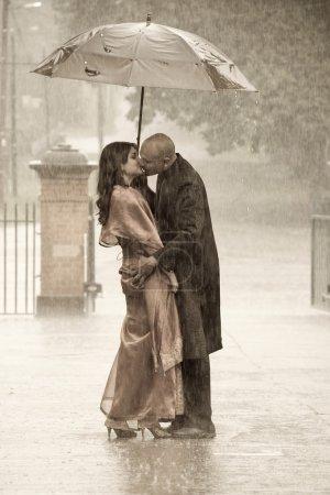 Photo pour Couple indien sous la pluie, parapluie holding homme et femme baiser - image libre de droit