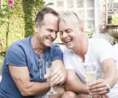 Pohledný gay pár sdílení intimní chvíli nad sklenkou šampaňského