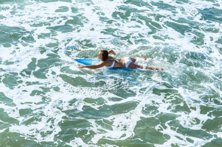 Young attractive surfer girl at the beach with surfboard