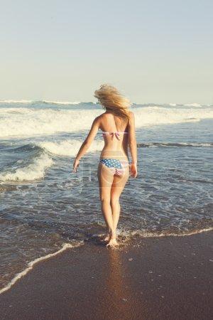 Young happy blonde having fun on beach in American Bikini