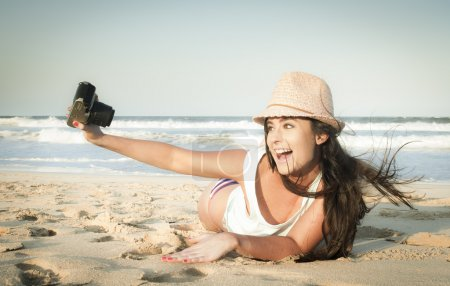 Young attractive girl taking photos with camera at the beach