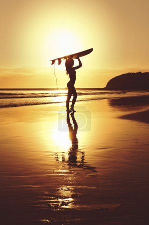 Young attractive surfer girl on beach with surfboard at sunrise