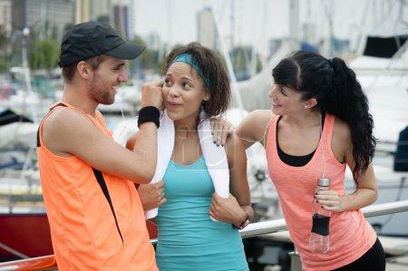 Photo pour Groupe de jeunes coureurs attrayants bavardant après une séance d'exercice - image libre de droit