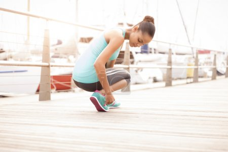 Close up of runner tying shoe laces on wooden boardwalk