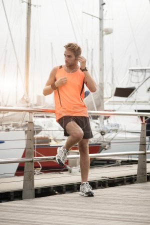 Young attractive guy leaning against railing with exercise gear