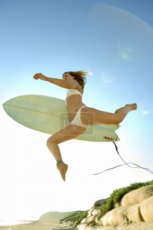 Photo for Young attractive surfer girl with surfboard at beach - Royalty Free Image