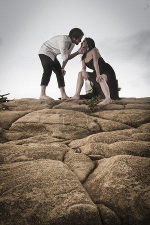 Happy attractive couple flirting on beach rocks under cloudy skies