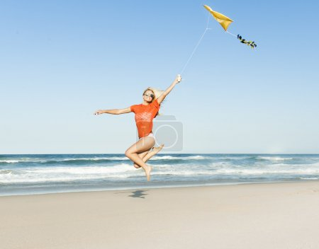 Young happy girl jumping on beach with yellow kite