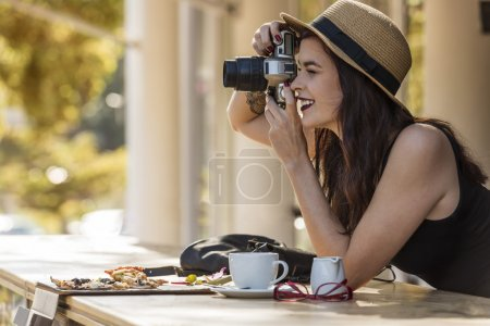 young beautiful traveler happily taking photos with camera at ca