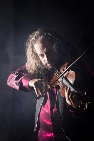 handsome man playing classical violin through blue smoke