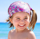 Happy smiling little girl on clear and tropical sea background