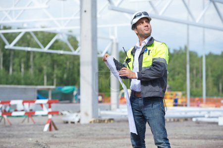 Photo for Civil engineer at construction site is inspecting ongoing works according to design drawings. - Royalty Free Image