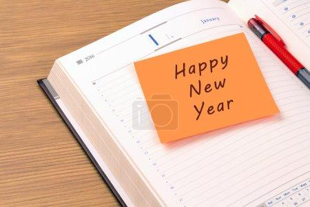 Photo pour Orange note collante sur un nouvel organisateur de bureau année 2016. Bonne année - image libre de droit
