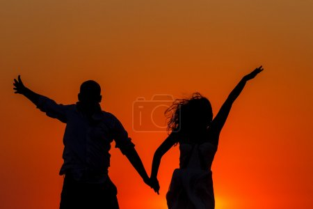 Romantic sunset and silhouettes of lovers