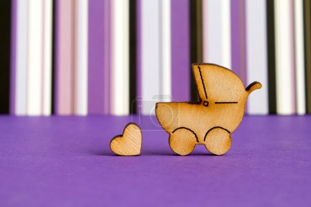 Wooden icon of baby carriage and little heart on purple striped