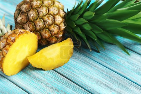 Photo for Ripe fresh  pineapples on a blue wooden background - Royalty Free Image