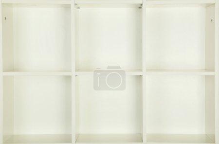 Empty shelves in white wooden rack