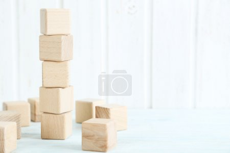 Photo for Wooden toy cubes on a blue wooden table - Royalty Free Image
