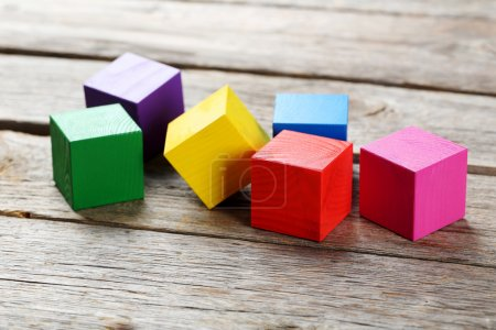 Photo for Colorful wooden toy cubes on a grey wooden background - Royalty Free Image