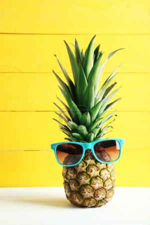 Photo pour Ananas mûr avec des lunettes de soleil sur une table en bois blanc - image libre de droit