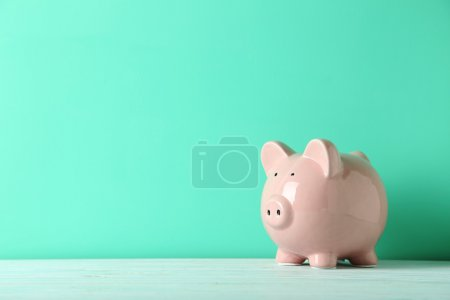 Pink piggy bank on wooden table