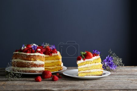 Photo for Delicious biscuit cake with berries on plate on grey wooden table - Royalty Free Image