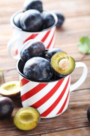 ripe plums in mugs
